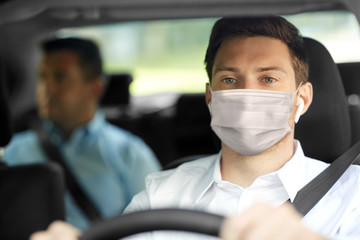 health protection, safety and pandemic concept - male taxi driver wearing face protective medical mask driving car with passenger Fototapete