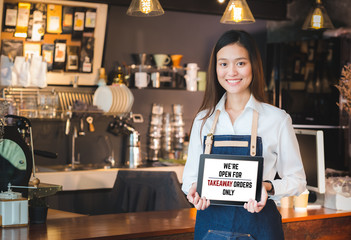asian barista holding tabblet sign we're open for takeaway orders only infront of...