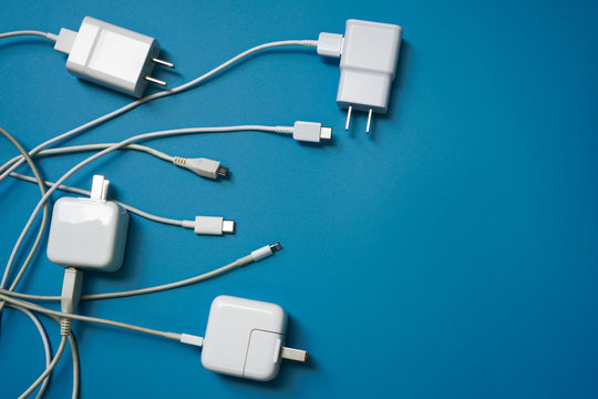 Top view or flat lay of White mobile power charger and USB in multiple types laid disorderly and mess on blue pvc sheet texture background , energy management concept ,with copy space