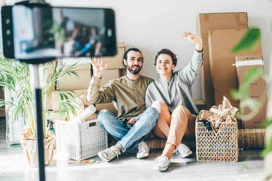 Lovely joyful young couple with belongings packed in different boxes sits on floor filming video with mobile phone in new apartment on moving day.
