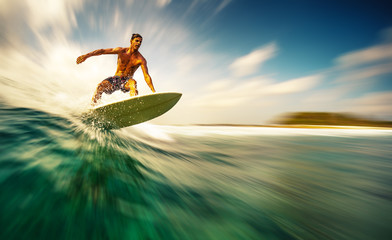 Wall Mural - Young athletic surfer rides the wave in tropics with splashes. Sultans surf spot in Maldives. Motion blurred version