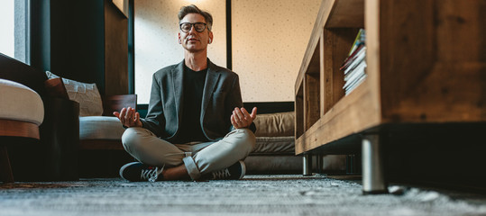 Mature businessman doing yoga meditation in office lounge Wall mural
