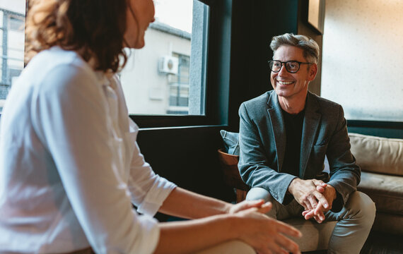 Businessman talking with female colleague in office lobby