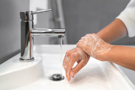 Hand washing lather soap rubbing wrists handwash step woman rinsing in water at bathroom faucet sink. Wash hands for COVID-19 spreading prevention. Coronavirus pandemic outbreak.
