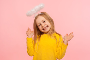 Playful angelic little girl raising arms and looking at camera with toothy smile, gesturing oops, i don't know, it wasn't me, joyful child denying guilt. indoor studio shot isolated on pink background Fototapete