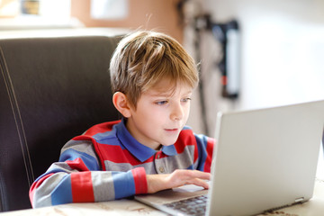 Little school kid making school homework on computer. Child learning on pc. Hard-working boy making exercise during quarantine time from corona pandemic disease. Homeschooling concept.