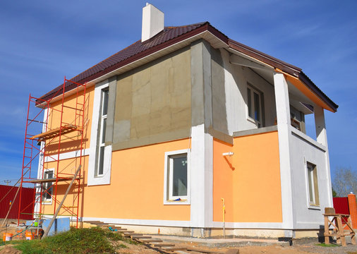 Painting renovation a modern house with stucco house finish, stucco siding and metal roof using scaffolding.