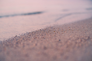 Fototapete - sandy beach and the edge of the water, macro shot, seashore at sunset, abstract natural background and texture retro tinted