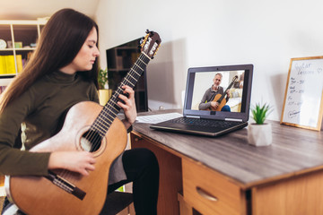 Focused girl playing acoustic guitar and watching online course on laptop while practicing at home....