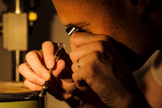 Craftsman appraising faceted gemstone.