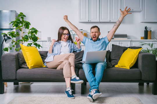 Young couple celebrating money win after betting online at bookmaker's website