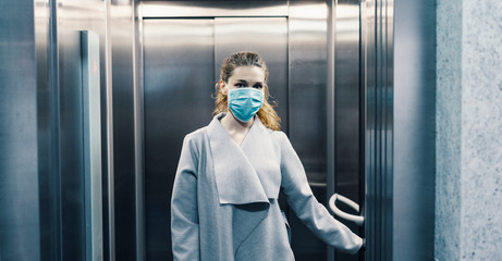 Person wearing face mask is using elevator