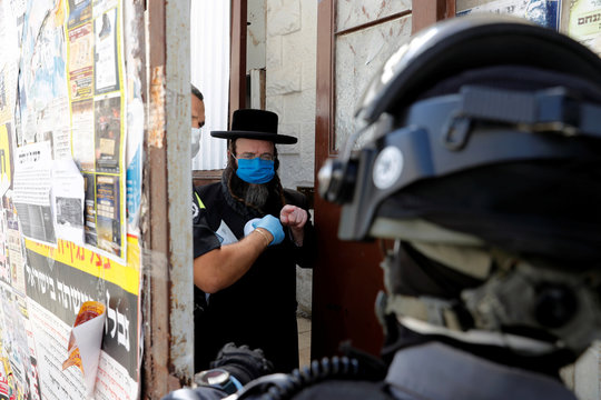 Israeli police question an ultra-Orthodox Jewish man for defying government restrictions set in place to curb the spread of the coronavirus disease (COVID-19), in Mea Shearim neighborhood of Jerusalem