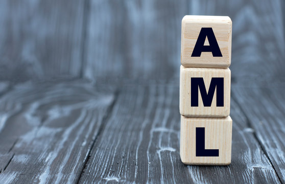 concept of the word AML on cubes on a wooden gray background