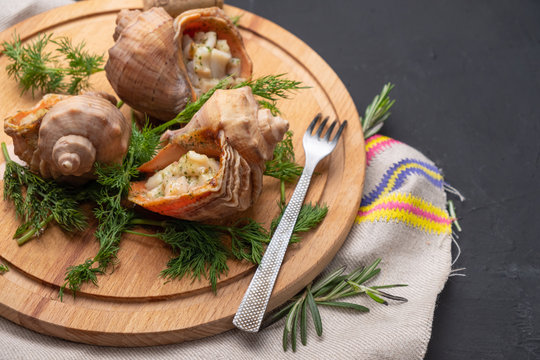 rapa whelk, clams with dill on a wooden round board on a dark background