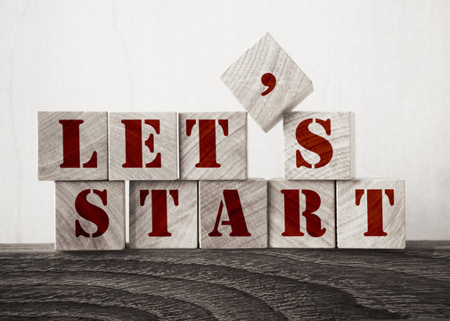 the words let's start in old wood type - wooden cubes. Business startup concept