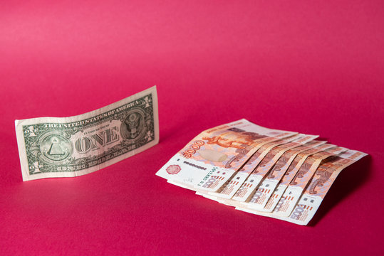 the us dollar puts pressure on paper five thousand ruble banknotes on a maroon background. dollar puts pressure ruble