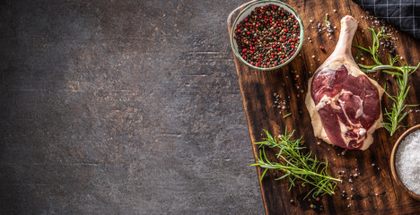 Top view of duck leg preparaton in a dark rustic environment with wooden cutting board with ingredients and seasonings covering half of the picture with dark metalic background Papier Peint