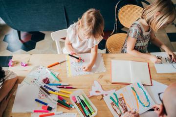 Top view two preschooler female children indoor at home drawing