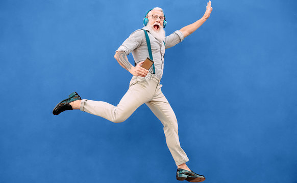 Senior crazy man jumping while listening music with wireless headphones - Hipster old guy having fun dancing outdoor - People happiness and elderly technology addicted concept - Blue background