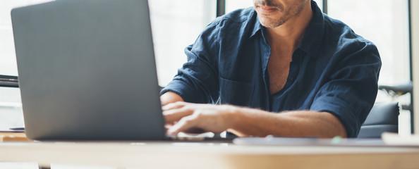 Man working on laptop at bright studio Fotomurales