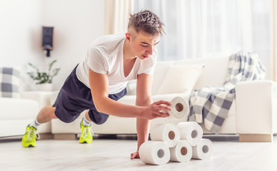 Fit young man creatively using excess toilet paper rolls for home plank and pushups workout in the living room Fotobehang