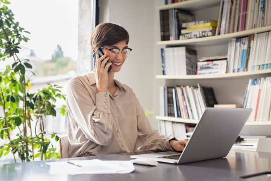 Business woman using laptop and talking on phone