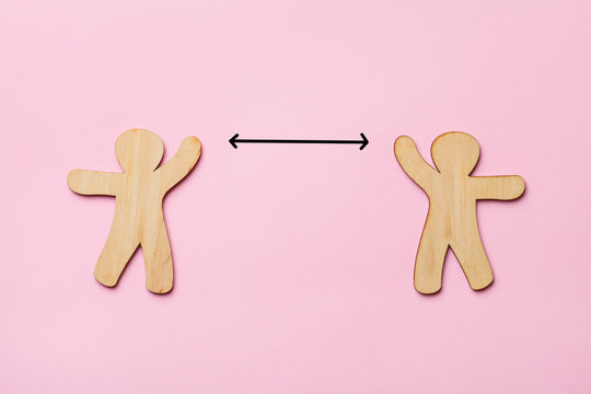 keep distance concept, two wooden people on pink background, preventive measures, infection control