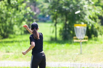 Fototapeta Young woman playing flying disc sport game in the park obraz