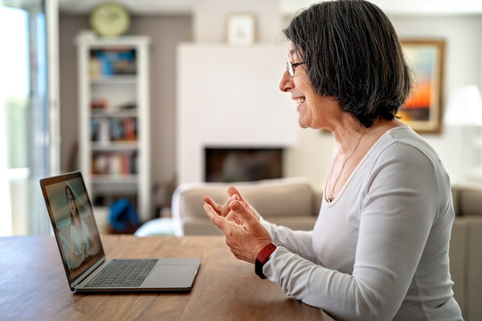 Adult  woman having video chat online on laptop with her granddaughter at home during quarantine isolation pandemic.  Senior lifestyle. Teacher giving online lesson to student from home.