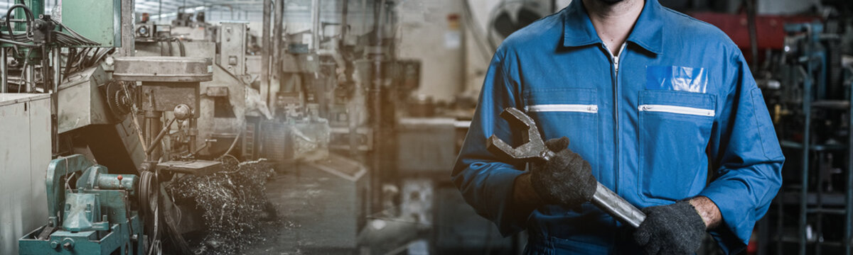 Close up image engineer men wearing uniform safety and holding wrench tool in factory background. banner layout.