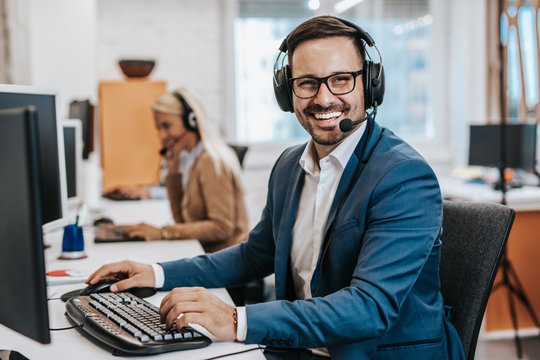 Handsome male customer service agent working in call center office as a telemarketer.
