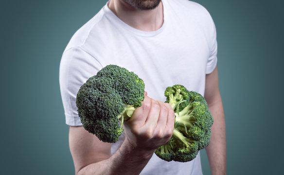 Junger Mann trainiert mit Brokkoli