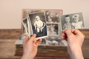 Wall Mural - old man's male hands hold old retro family photos over an album with vintage monochrome photographs in sepia color, genealogy concept, ancestral memory, family ties, childhood memories