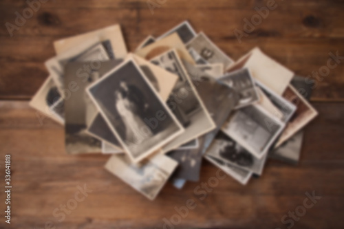 Wall mural old vintage monochrome photographs in sepia color are scattered on a wooden table, the concept of genealogy, the memory of ancestors, family ties, memories of childhood