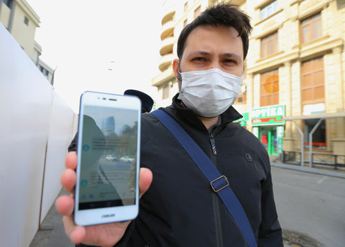 A man shows his mobile phone with a permission to leave home received in a text message, in Baku