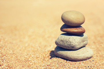 Zelfklevend Fotobehang Stenen in het Zand balanced stacked pebble stones on sand background.