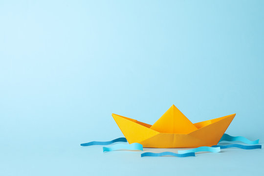 Paper boat and waves on blue background, space for text