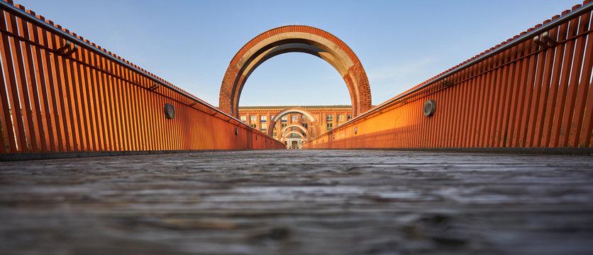 Symetrische Brücke aus braunem Holz und orangenem Metall führt zur alten Spinnerei in Plochingen