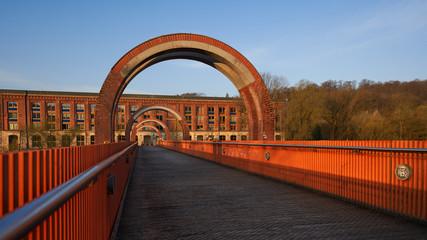 Brücke aus braunem Holz und orangenem Metall führt zur alten Spinnerei in Plochingen