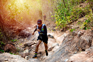A man Runner of Trail and athlete's feet wearing sports shoes for trail running in the forest Fotomurales
