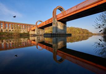 Altes Spinnerei Gebäude spiegelt sich am frühen kalten morgen im Wasser des Neckars