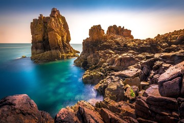 Beautiful shot of a landscape of cliffs and a calm sea on the background Wall mural