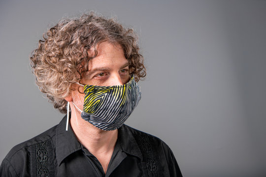 Portrait of a middle aged man wearing a homemade cloth mask during the Covid-19 outbreak. He looks to his left.