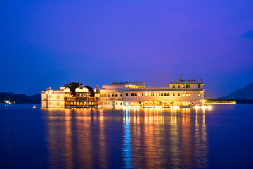 Wall Mural - Romantic luxury India travel tourism - Lake Palace (Jag Niwas) complex on Lake Pichola in twilight, Udaipur, Rajasthan, India