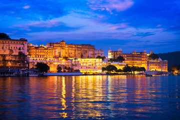 Wall Mural - View of famous romantic luxury Rajasthan indian tourist landmark - Udaipur City Palace in the evening twilight with dramatic sky - panoramic view. Udaipur, India