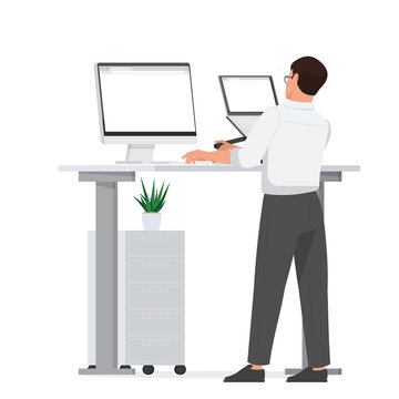 A man works at a computer while standing at a table.