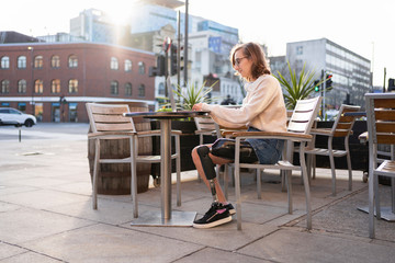 Young woman with leg prosthesis sitting in a sidewalk cafe in the city using laptop