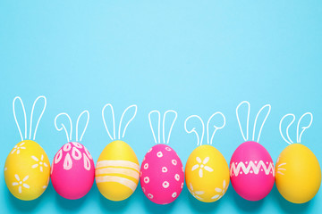 Fotobehang - Bright Easter eggs with cute bunny ears and space for text on light blue background, flat lay