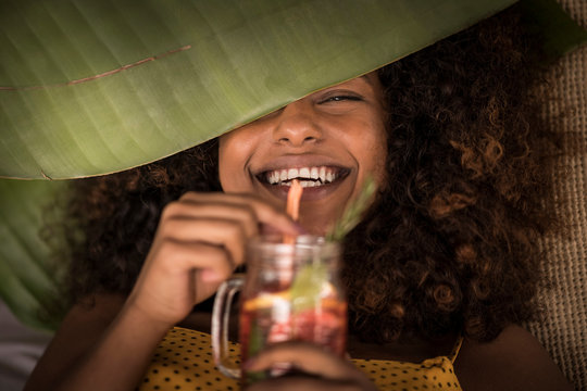 Close-up of happy woman drinking fresh ice tea drink
